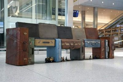 Large bench made of suitcases, in airport departure hall.