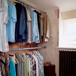 Scaffold tubes as rails for clothing in the wardrobe.