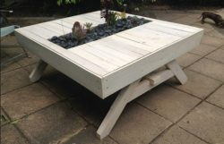 Garden table made from pallets, with a planter in the tabletop center.