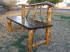 Bench frame from branches and seat made from scaffold boards.