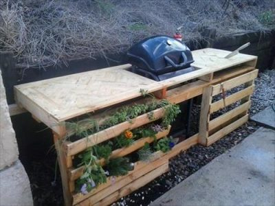 Pallets are used to make this outside kitchen with integrated planters for herbs.