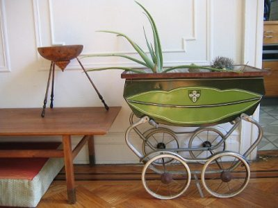 Practical use of old pram as holder for plant pots.