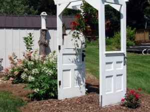 Two doors combined to make a romantic arch for roses in the garden.
