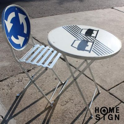 Folding table and chair made partly with reclaimed street signal boards.