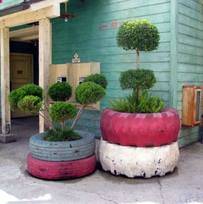 Corner protection made from reclaimed tires, filled with soil and in use as planters.